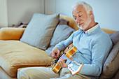 Senior man playing guitar on living room sofa