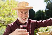Senior man drinking red wine in garden