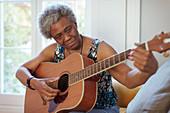 Active senior woman playing guitar