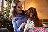 Teenage girl petting dog in Christmas gift box