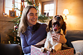 Happy girl with yawning dog in Christmas gift box
