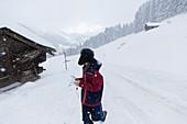 Teenage boy walking outside snowy mountain cabin