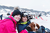 Portrait brother and sister with dog on ski slope