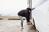 Portrait man tying boot shoelaces at motor home