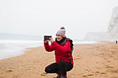 Woman using camera phone on snowy beach