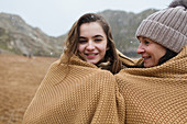 Mother and daughter wrapped in a blanket on beach