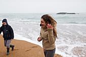 Playful teenage girl on snowy winter beach