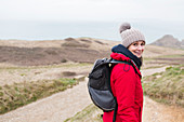 Portrait woman with backpack hiking on remote path