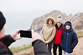 Man photographing family on cliff