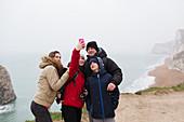 Family taking selfie on cliff overlooking ocean
