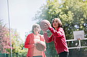 Active senior women friends playing basketball