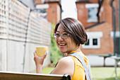Portrait woman drinking tea in yard