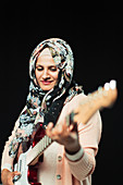 Woman in floral hijab playing electric guitar