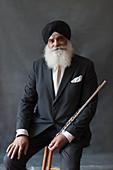 Portrait senior man in turban holding flute
