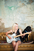 Young woman with dog playing electric guitar
