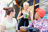 Waitress serving smoothies to women friends