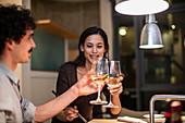 Couple toasting white wine glasses in apartment kitchen