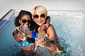 Portrait exuberant friends drinking champagne in hot tub