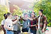 Happy male friends toasting drinks over barbecue grill