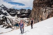 Female hikers hiking snowy mountain slope, Canada