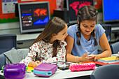 school students using smart phone at desk