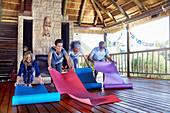 People unrolling yoga mats in hut