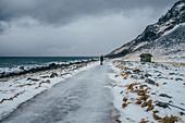 Woman walking along icy beach, Lofoten Islands, Norway