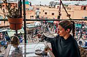 Woman enjoying tea on balcony, Marrakesh, Morocco