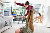 Father and son playing on living room floor