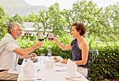 Mature couple toasting wine glasses