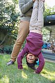 Playful boy hanging upside down in backyard