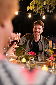 Happy man toasting wine glass at dinner garden party