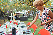 Woman setting table for dinner garden party