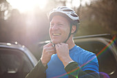 Portrait smiling man fastening bike helmet