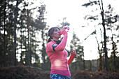 Female runner drinking from water bottle in woods