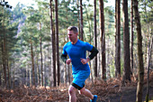 Man running on trail in sunny autumn woods