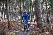 Man mountain biking on trail in autumn woods