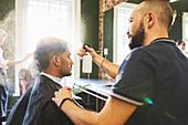 Male barber spraying hair of man in barbershop