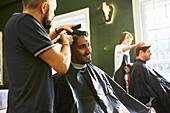 Smiling man receiving haircut at barbershop