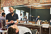 Male barber preparing to shave face of customer