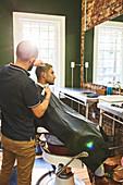 Man receiving haircut at barbershop