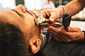 Close up man receiving a shave in barbershop