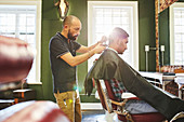 Focused male barber giving customer a haircut