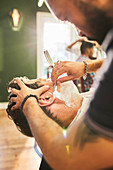 Male barber giving customer a shave in barbershop