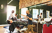 Male barber preparing to steam face of customer