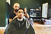 Male barber giving customer haircut in barbershop