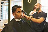 Male barber shaving hair of customer in barbershop