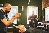 Male barber standing over customer in barbershop