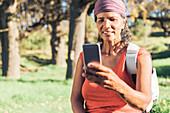 Female hiker using smart phone in sunny woods