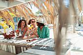 Happy women drinking cocktails at beach bar